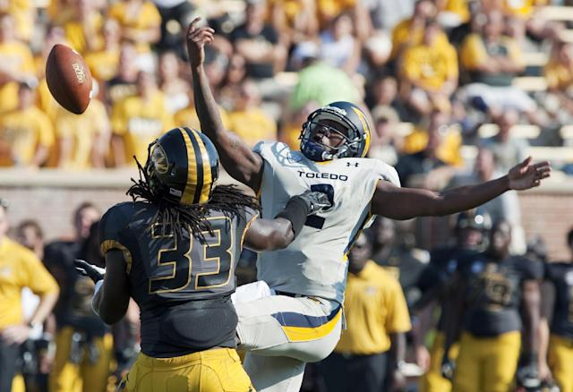 FILE - In this Sept. 7, 2013, file photo, Missouri's Markus Golden, left, reaches to intercept the ball that slipped out of Toledo quarterback Terrance Owens' hand, right, before returning it for a touchdwon during the third quarter of an NCAA college football in Columbia, Mo. Golden's 70-yard interception return against Toledo was one of Missouri's six picks this year, just one shy of its total from all of last season. The defense will get its toughest test so far against a high-octane Indiana offense, one it will face without suspended captain Andrew Wilson for the first half. (AP Photo/L.G. Patterson, File)