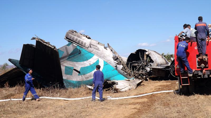 Members of Myanmar Fire Brigade team gather near a damaged Air Bagan passenger plane in Heho, Shan State, Myanmar, Tuesday, Dec. 25, 2012. The Air Bagan flight packed with Christmas tourists crash-landed on a road in central Myanmar on Tuesday, killing two people and injuring 11, officials said. Four foreigners were among the injured, state television reported. It said the fatalities included an 11-year-old passenger believed to be a Myanmar citizen and a man riding a motorcycle on the road where the plane came down. (AP Photo)