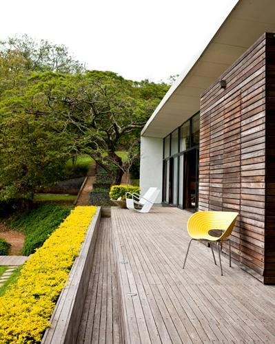 Colorful plants border the terrace of a Bauhaus-inspired home situated on a hillside outside Durban, South Africa. The yellow Tom Vac chair is by Ron Arad for Vitra, and the wire rocking chair is by Egg Designs, the firm of the homeowners, Greg and Roche Dry.  (Photo: Sean Laurenz)