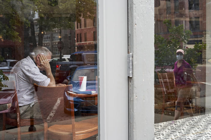 A woman wearing a face mask is reflected in the window of a coffee shop during the coronavirus pandemic in downtown Omaha, Neb., Friday, Aug. 7, 2020. (AP Photo/Nati Harnik)