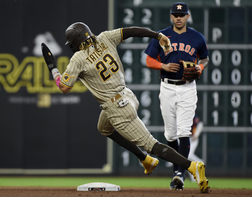 San Diego Padres' Fernando Tatis Jr. (23) runs to third on Eric Hosmer's single as Houston Astros shortstop Carlos Correa watches during the fourth inning of a baseball game, Sunday, May 30, 2021, in Houston. (AP Photo/Eric Christian Smith)