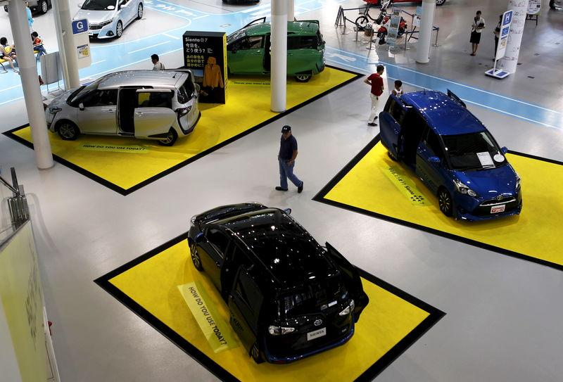 A visitor walks between Toyota Motor Corp's cars displayed at the company's showroom in Tokyo