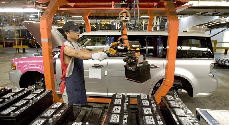 Worker Nick Aphayvong prepares to install a battery into a Ford Flex on the assembly line at the company's Oakville Plant June 3, 2008. REUTERS/Fred Thornhill