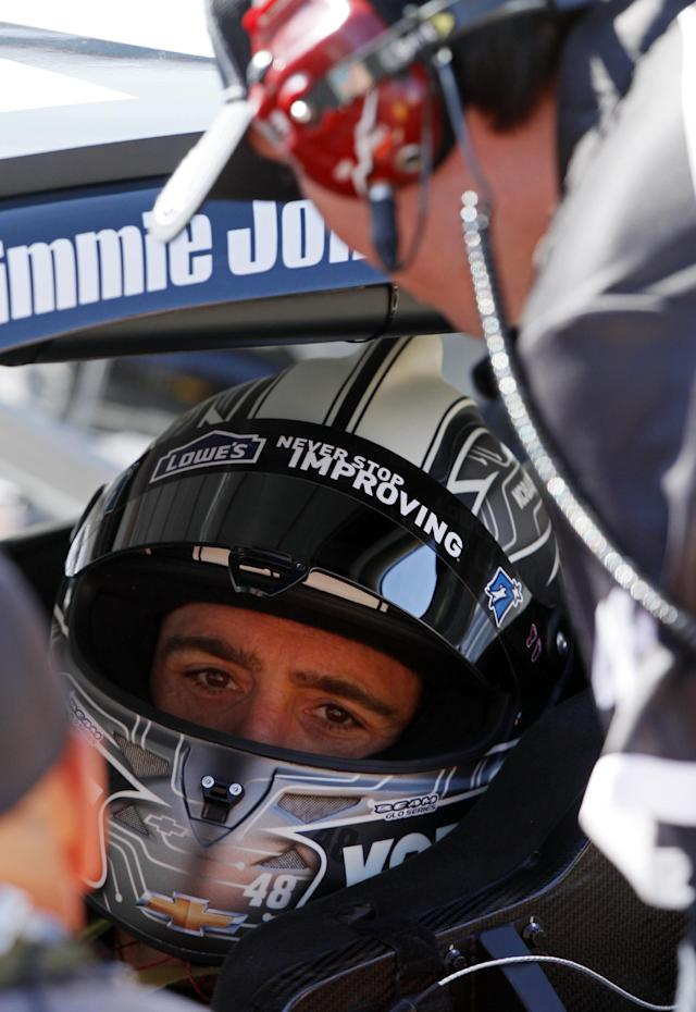 Driver Jimmie Johnson (48) talks to teammates before practice for the NASCAR Sprint Cup series auto race at Bristol Motor Speedway on Friday, March 14, 2014, in Bristol, Tenn. (AP Photo/Wade Payne)