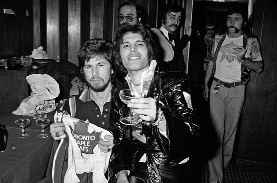 <p>Queen holds up the Toronto Maple Leaf jerseys they were gifted while performing in Canada in 1977. </p>
