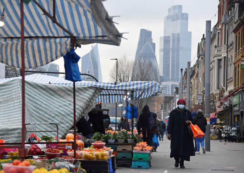 FILE PHOTO: People shop at market stalls, with skyscrapers of the CIty of London financial district seen behind, in London