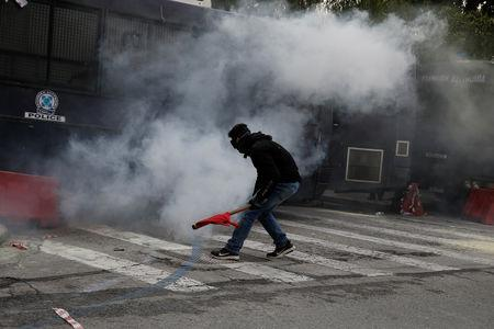 A protester moves amid tear gas smoke as Greek school teachers scuffle with riot police during a demonstration against government plans to change hiring procedures in the public sector in Athens, Greece, January 11, 2019. REUTERS/Costas Baltas