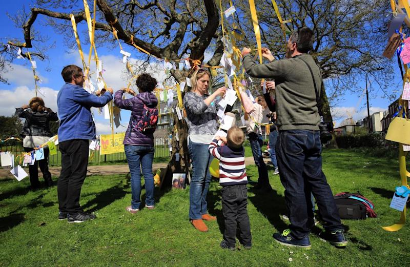 Huge support: Family and friends tie yellow ribbons to trees (PA)