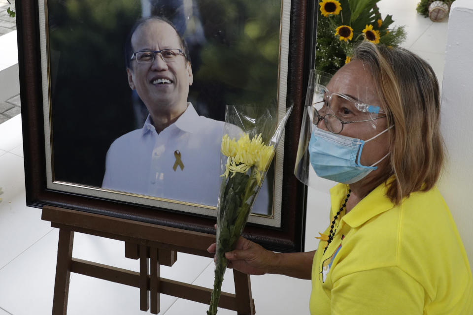 A supporter sits beside a picture of former Philippine President Benigno Aquino III beside his tomb on Saturday, June 26, 2021 at a memorial park in suburban Paranaque city, Philippines. Aquino was buried in austere state rites during the pandemic Saturday with many remembering him for standing up to China over territorial disputes, striking a peace deal with Muslim guerrillas and defending democracy in a Southeast Asian nation where his parents helped topple a dictator. He was 61. (AP Photo/Aaron Favila)