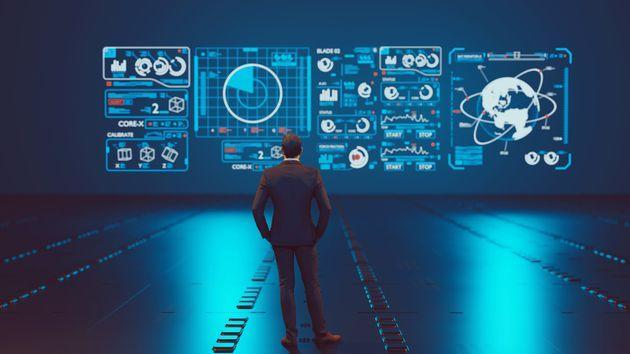 Man stands in front of a big hologram screen which has different symbols. He is analyzing data. Concept of data analysis and data complexity. (Photo: mikkelwilliam via Getty Images)