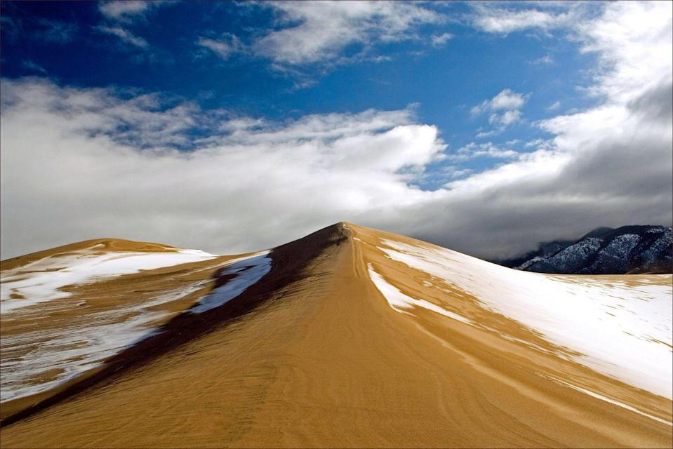 <p>The Great Sand Dunes National Park in southern Colorado is known for its huge sand dunes, obviously. The otherworldly look of the huge mounds of sand is even cooler when it's dusted in snow. </p>