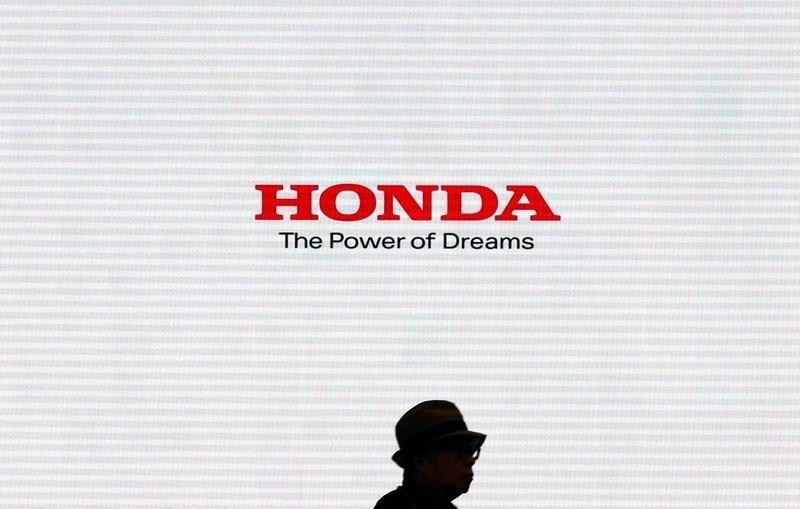 Man is silhouetted against a logo of Honda Motor at the company showroom in Tokyo