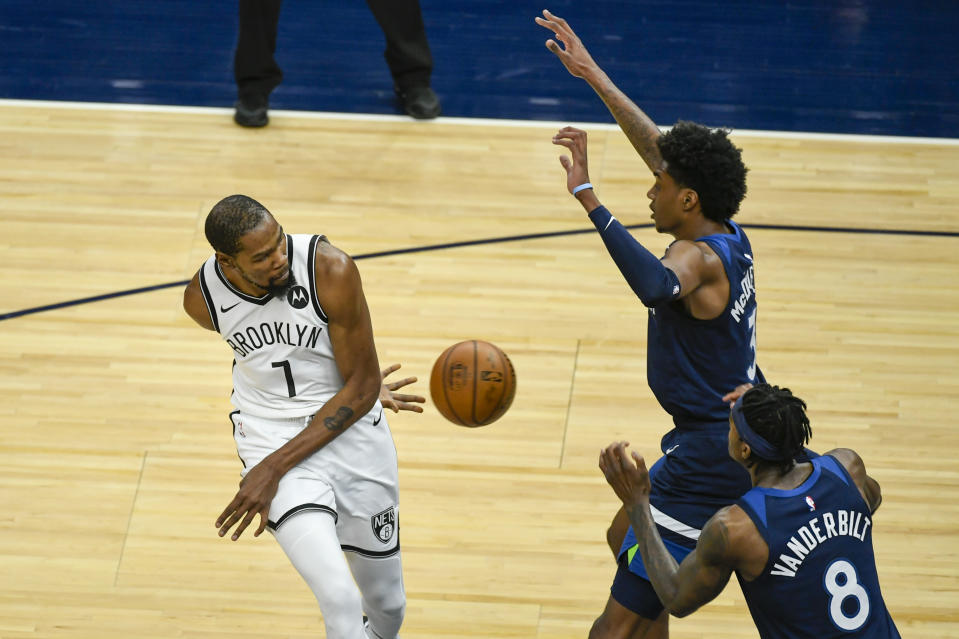 Brooklyn Nets forward Kevin Durant (7) passes the ball behind his back and around Minnesota Timberwolves forward Jaden McDaniels (3) and Timberwolves forward Jarred Vanderbilt (8) during the first half of an NBA basketball game Tuesday, April 13, 2021, in Minneapolis. (AP Photo/Craig Lassig)