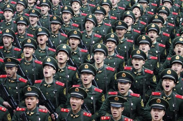 Recruits of the People's Liberation Army (PLA) shout slogans during a handover ceremony on a rainy day at a military base in Hangzhou, Zhejiang province February 10, 2012.