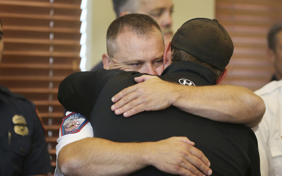 Draper Battalion Chief Bart Vawdrey hugs a fellow firefighter during a press conference in Draper, Utah, on Tuesday, Aug. 14, 2018. Draper Battalion Chief Matthew Burchett was killed on Monday night while fighting the largest blaze in California history, the Mendocino Complex fire north of San Francisco. (Jeffrey D. Allred/The Deseret News via AP)