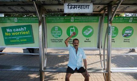 A man exercises on a bus stop with hoardings promoting digital payments in Mumbai