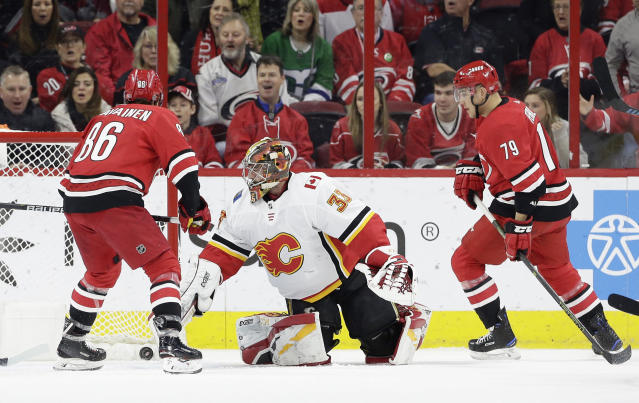Carolina Hurricanes' Teuvo Teravainen (86), of Finland, scores against Calgary Flames goalie David Rittich while Hurricanes' Micheal Ferland (79) looks on during the first period of an NHL hockey game in Raleigh, N.C., Sunday, Feb. 3, 2019. (AP Photo/Gerry Broome)