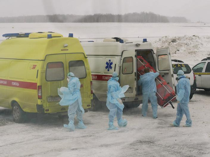 Medical staff members preparing equipment to meet passengers of a military plane, which evacuated citizens of Russia and ex-Soviet countries from China's Wuhan province, the epicenter of an outbreak of the coronavirus epidemic, are seen through a bus window at the Roshchino International Airport outside Tyumen, Russia February 5, 2020.
