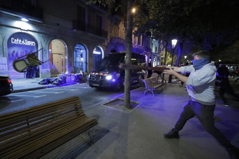 Chairs are thrown at a police van in Barcelona, Spain, Thursday, Oct. 17, 2019. Catalonia's separatist leader vowed Thursday to hold a new vote to secede from Spain in less than two years as the embattled northeastern region grapples with a wave of violence that has tarnished a movement proud of its peaceful activism. (AP Photo/Manu Fernandez)