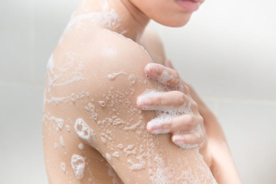Woman using soap in the shower.