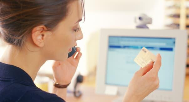 Young woman in front of computer, using telephone,holding credit card