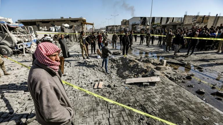 People inspect the scene of a car bomb in the Turkish-controlled town of Al-Bab in the north of Syria's Aleppo province