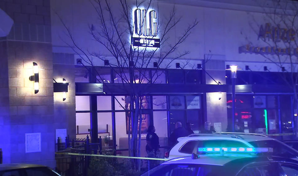 """In this image from video provided by WSB-TV, police officers stand outside Old Lady Gang restaurant Friday, Feb. 14, 2020, in East Point, Ga. Three people were shot and wounded at the restaurant just outside Atlanta that's owned by singer and """"Real Housewives of Atlanta"""" star Kandi Burruss. A man entered the Old Lady Gang restaurant and targeted another man, East Point police Capt. Allyn Glover told news outlets. Police say two bystanders were also shot, and all three shooting victims suffered non-life-threatening injuries. (WSB-TV via AP)"""