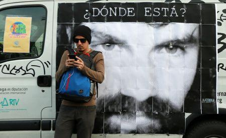 "A man looks at his cell phone in front of a portrait of Santiago Maldonado, a protester who has been missing since security forces clashed with indigenous activists in Patagonia on August 1, 2017, at a demonstration to demand actions to find him, in Buenos Aires, Argentina September 1, 2017. Words on the banner read ""Where is he?"". Picture taken September 1, 2017. REUTERS/Marcos Brindicci"