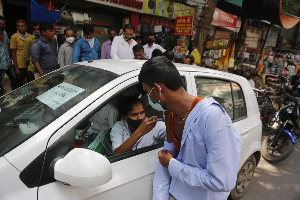 A health worker administers the vaccine for COVID-19 during a vaccination drive at a market place in Ahmedabad, India, Friday, Sept. 24, 2021. (AP Photo/Ajit Solanki)