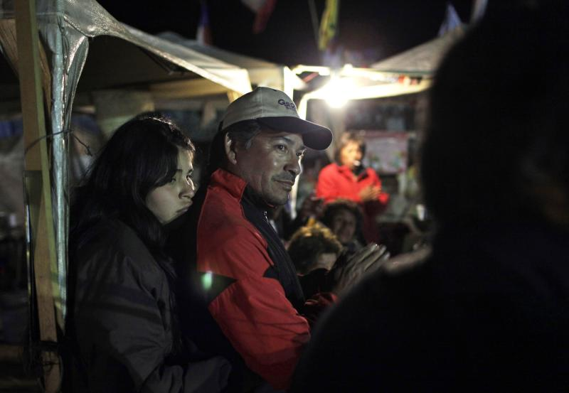 Alberto Segovia, brother of trapped miner Dario Segovia, and his daughter Carla Belgica, stand at the relatives camp outside the San Jose mine, near Copiapo, Chile, Monday, Oct. 11, 2010. The33  miners became trapped when the gold and copper mine collapsed on Aug. 5 and are expected to be rescued starting late Tuesday or early Wednesday. (AP Photo/Jorge Saenz)