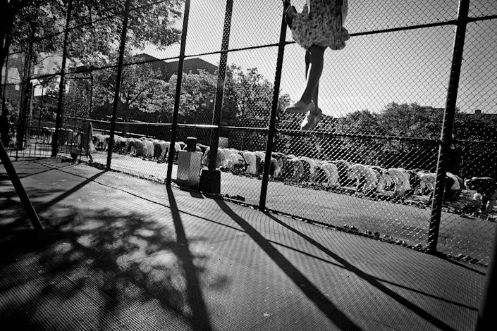 <p>A child plays in a swing nearby during morning Eid prayers in Travers Park in Jackson Heights, Queens, N.Y., in September 2015, because it is a big Muslin holiday with a large crowd, the city allows them to pray in the park every year. (Photo: Yunghi Kim/Contact Press Images) </p>