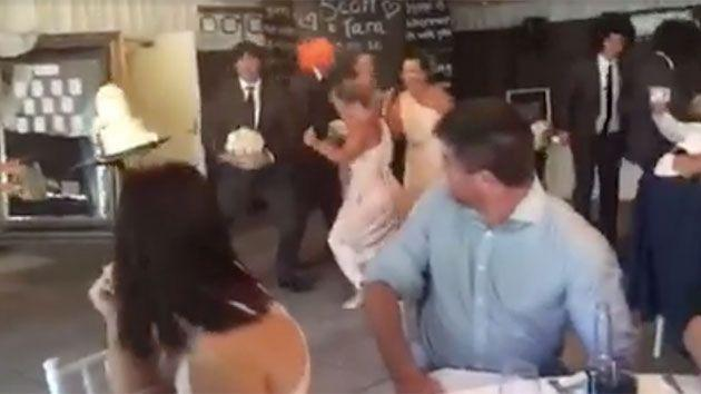The goofy groomsman squats down and hits the cake stand, sending it flying across the dance floor. Photo: Wendy Collier