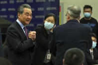 Chinese Foreign Minister Wang Yi, left, is greeted by attendees as he arrives the Lanting Forum on bringing China-U.S. relations back to the right track, at the Ministry of Foreign Affairs office in Beijing on Monday, Feb. 22, 2021. Wang called on the U.S. Monday to lift restrictions on trade and people-to-people contacts while ceasing what Beijing considers unwarranted interference in the areas of Taiwan, Hong Kong, Xinjiang and Tibet. (AP Photo/Andy Wong)