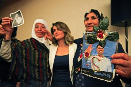 Basak Demirtas (C), wife of Selahattin Demirtas, who has been in jail for a year and a half, is flanked by women holding pictures of the Kurdish leader who is challenging Turkish President Recep Tayyip Erdogan at the polls
