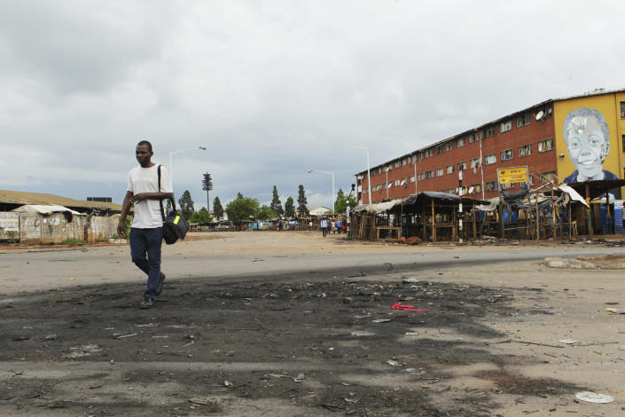 A man walks past a deserted street following demonstrations over hike in fuel prices in Harare, Zimbabwe, Tuesday, Jan,15, 2019. Soldiers moved in to disperse crowds at the busy intersection and transport hub in Harare amid Zimbabwe's biggest unrest since deadly post-election violence in August. (AP Photo/Tsvangirayi Mukwazhi)