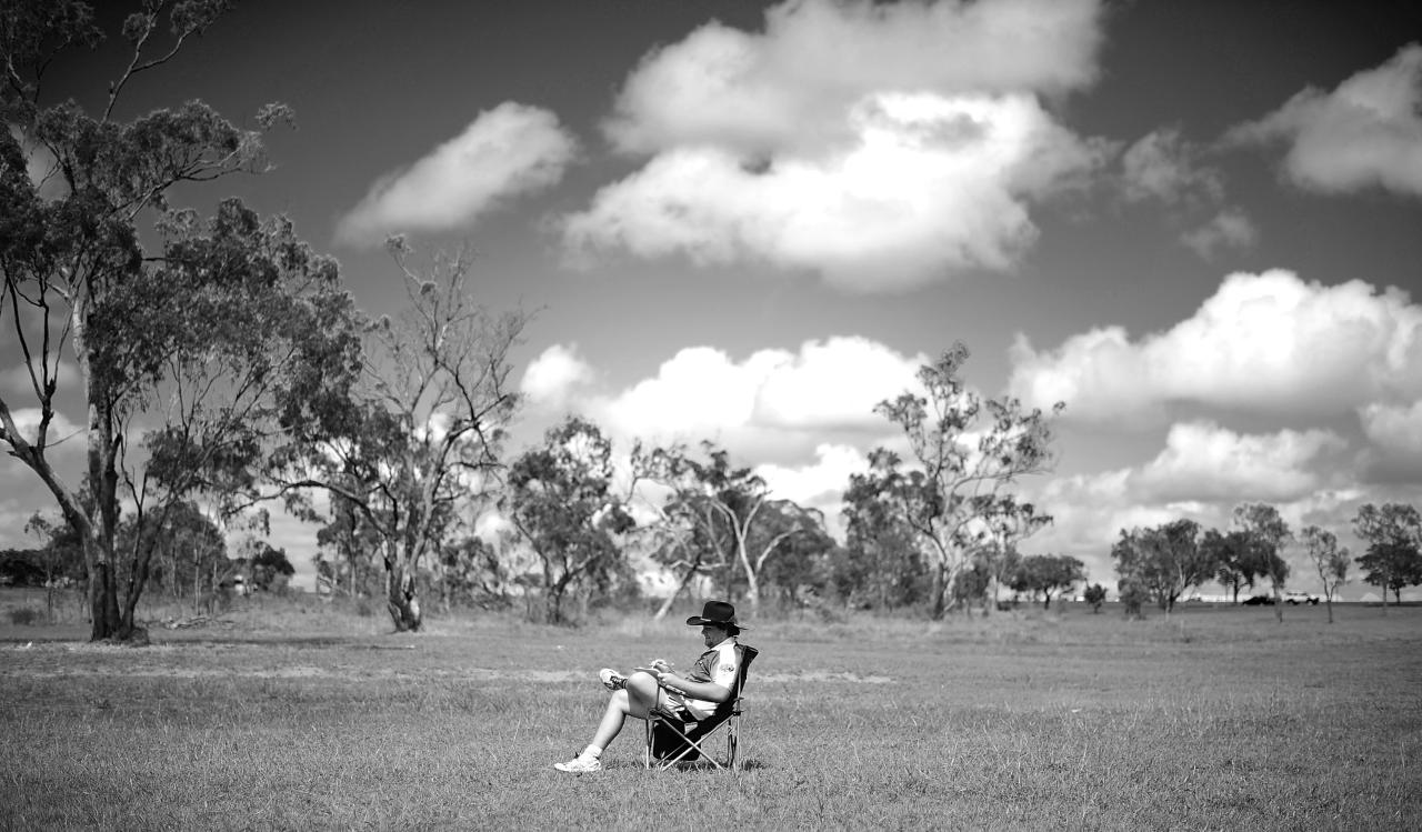 CHARTERS TOWERS, AUSTRALIA - JANUARY 21:  (EDITORS NOTE: Image has been converted to black and white.) Dempsey McCoy from the team 'Wolf Pack' sits alone whilst scoring during the 2012 Goldfield Ashes cricket competition  on January 21, 2012 in Charters Towers, Australia. Every year the small outback town of Charters Towers in North Queensland hosts a cricket carnival named 'The Goldfield Ashes'. In 1948 the Charters Towers cricket Association extended an invitation to six teams to play on Foundation Day. From those six teams the carnival has grown to over 200 teams competing in 2012 making ot the largest cricket carnival in the Southern Hemisphere. Games are played on 58 different playing fileds including some which are privately owned.  The Goldfield  Ashes is one of the few sporting carnivals which caters for players of all levels of ability (Photo by Ian Hitchcock/Getty Images)