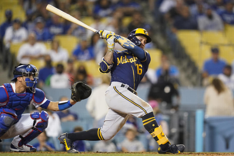 Milwaukee Brewers' Kolten Wong (16) doubles during the second inning of a baseball game against the Los Angeles Dodgers Friday, Sept. 1, 2021, in Los Angeles. Lorenzo Cain scored. (AP Photo/Ashley Landis)