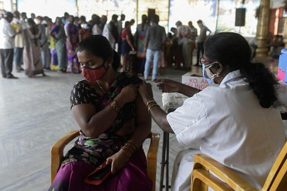 A health worker inoculates a woman with a dose of a Covid-19 vaccine (AFP via Getty Images)