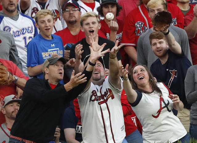 Fans reach for a ball tossed into the stands by Atlanta Braves left fielder Ronald Acuna Jr. during a baseball game against the Colorado Rockies,Friday, April 26, 2019, in Atlanta. (AP Photo/John Bazemore)