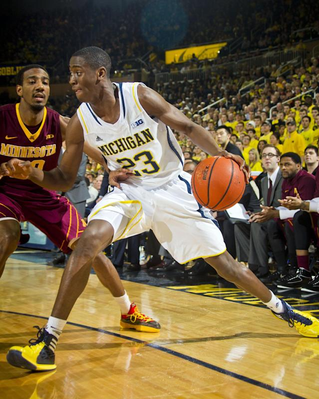 Minnesota guard Austin Hollins, left, defends Michigan guard Caris LeVert during the first half of an NCAA college basketball game in Ann Arbor, Mich., Saturday, March 1, 2014. (AP Photo/Tony Ding)