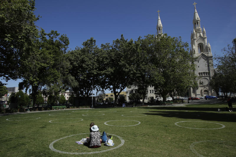 FILE - In this Saturday, May 23, 2020, file photo, a woman and child sit in a circle designed to help prevent the spread of the coronavirus by encouraging social distancing at Washington Square park in front of Saints Peter and Paul Church in San Francisco. An appeals court has upheld California Gov. Gavin Newsom's ban on in-person church services amid the coronavirus pandemic. The split ruling found that government's emergency powers override what in normal times would be fundamental constitutional rights. (AP Photo/Jeff Chiu, File)
