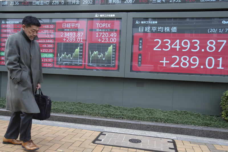 A man walks by an electronic stock board of a securities firm in Tokyo, Tuesday, Jan. 7, 2020. Shares are climbing in Asia following modest gains on Wall Street despite caution over rising tensions between the U.S. and Iran. (AP Photo/Koji Sasahara)