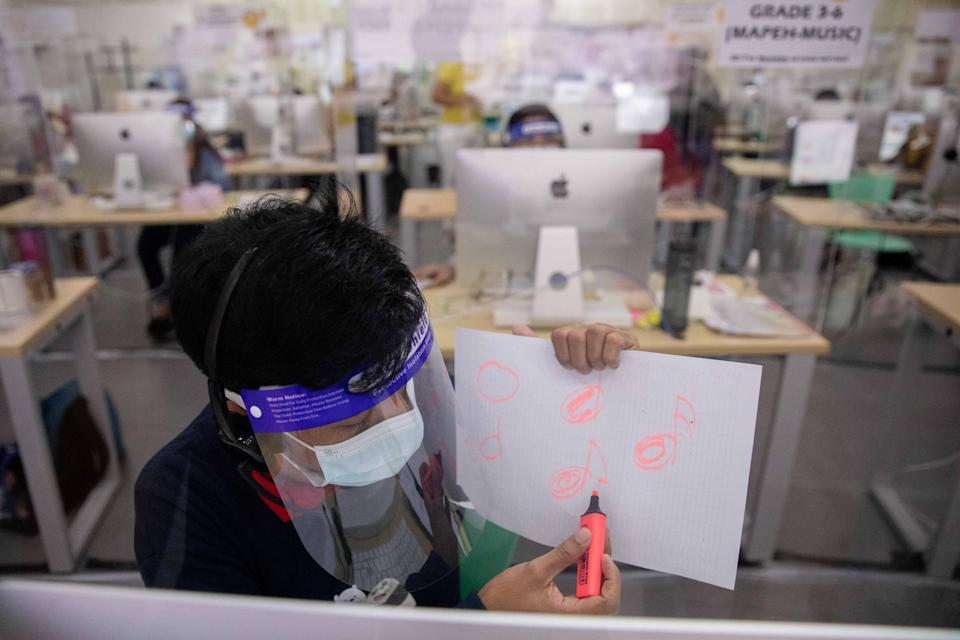 A teacher explains a lesson during a video call with a student through a hotline program, amid the coronavirus disease (COVID-19) outbreak, in Taguig City, Metro Manila, Philippines, October 7, 2020. Picture taken October 7, 2020. REUTERS/Eloisa Lopez