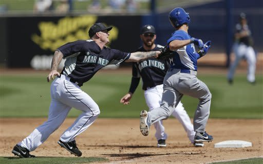 Seattle Mariners pitcher Jeremy Bonderman, left, tags out Kansas City Royals' Chris Getz on his way to first as Mariners first baseman Eric Hosmer, center, watches during the third inning of a spring training baseball game Tuesday, March 26, 2013, in Peoria, Ariz. (AP Photo/Gregory Bull)