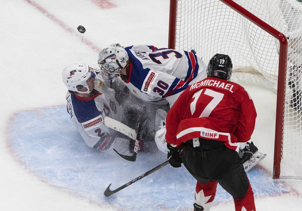 Canada's Connor McMichael (17) is stoped by U.S. goalie Spencer Knight (30) as Drew Helleson (2) slides into the net during the third period of the championship game in the IIHF World Junior Hockey Championship, Tuesday, Jan. 5, 2021, in Edmonton, Alberta. (Jason Franson/The Canadian Press via AP)