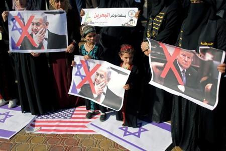 FILE PHOTO: Palestinians hold crossed-out posters depicting U.S. President Trump and Israeli PM Netanyahu during a protest against Bahrain's workshop, in the southern Gaza Strip