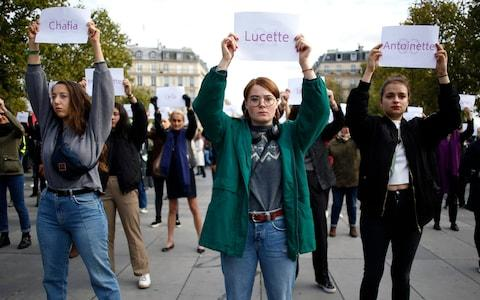 Activists hold placards with the names of women killed by their partners - Credit: AP Photo/Thibault Camus, File