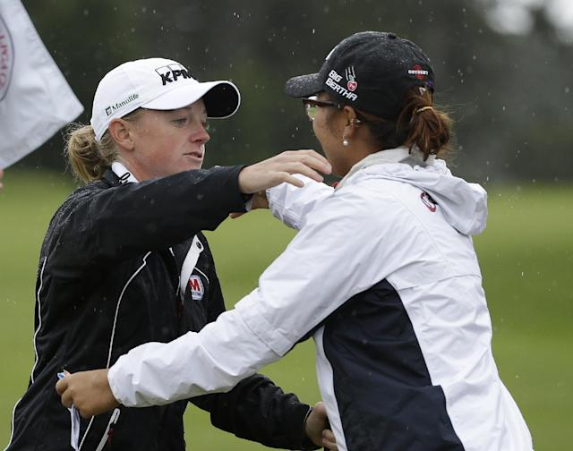 As rain falls, Stacy Lewis, left, is greeted on the ninth green of the Lake Merced Golf Club by Lydia Ko, right, of New Zealand, after finishing the second round of the Swinging Skirts LPGA Classic golf tournament on Friday, April 25, 2014, in Daly City, Calif. (AP Photo/Eric Risberg)