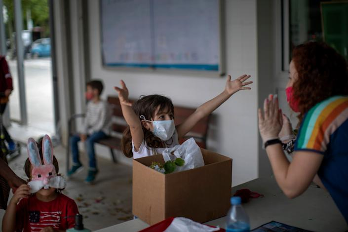 A primary school student gestures as if asking for a hug from her teacher at the end of the school year in Barcelona. (Photo: AP Photo/Emilio Morenatti)