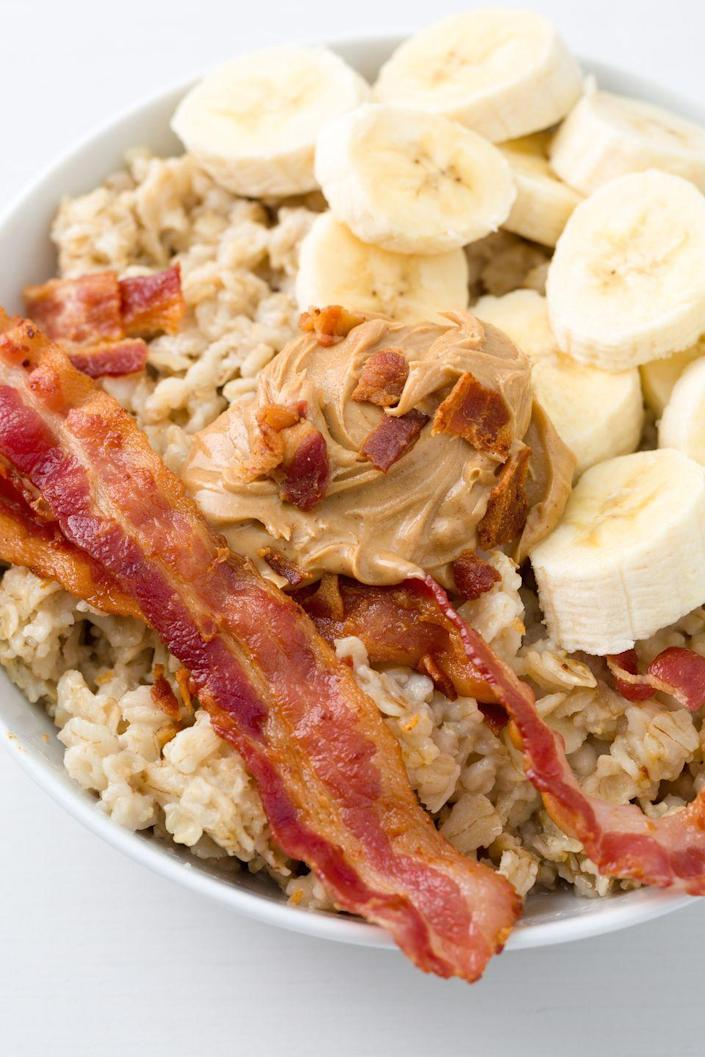"""<p>Elvis was known for his bizarre food cravings, including his love of bacon, banana, and peanut butter sandwiches. That combo is so good, we topped it on oatmeal.</p><p>Get the recipe from <a href=""""https://www.delish.com/cooking/recipe-ideas/recipes/a44491/elvis-oatmeal-recipe/"""" rel=""""nofollow noopener"""" target=""""_blank"""" data-ylk=""""slk:Delish"""" class=""""link rapid-noclick-resp"""">Delish</a>.</p>"""
